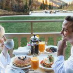 Couple enjoying room service breakfast on balcony at Montage Deer Valley