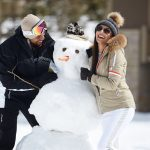 Couple laughs and builds snowman at Montage Deer Valley.