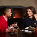 Couple enjoying romantic dinner by fireplace in Apex Steak