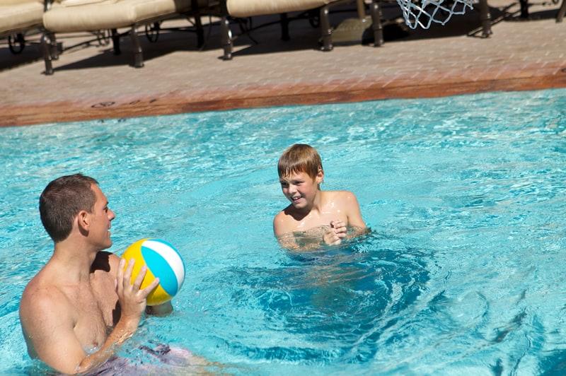 father and son playing in pool